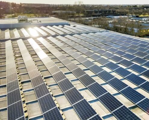 Commercial solar panels with sun shining on them